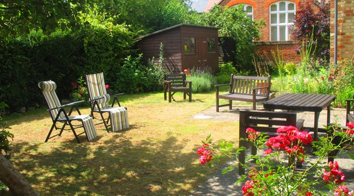 Sunny garden with tables and chairs where residents can enjoy the sunshine and a breath of fresh air