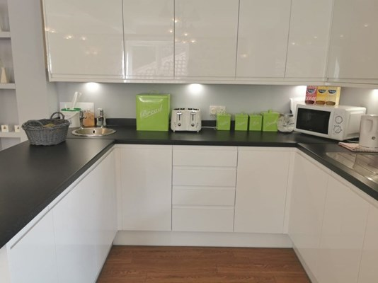 A bright white kitchen with black worktop