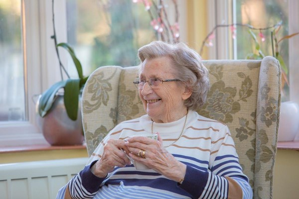 Seated resident smiling whilst holding a cup of tea