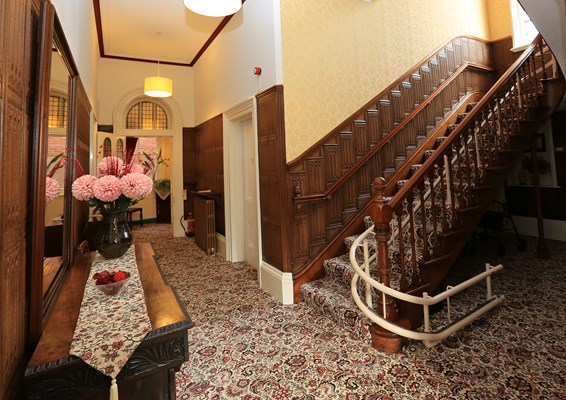 The hallway with wood panelled staircase and floral carpet