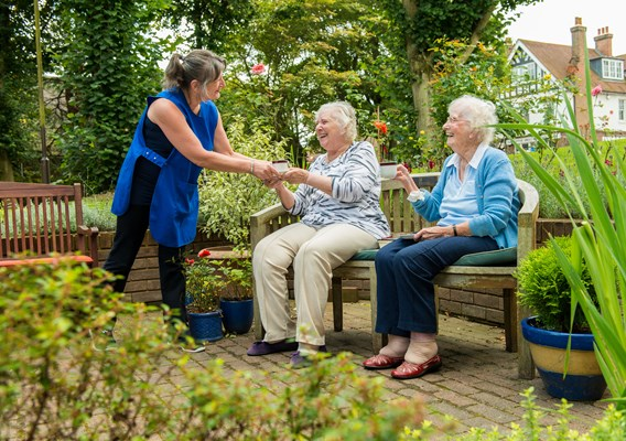 Two happy residents sitting on a bench in the garden being served tea by a member of staff