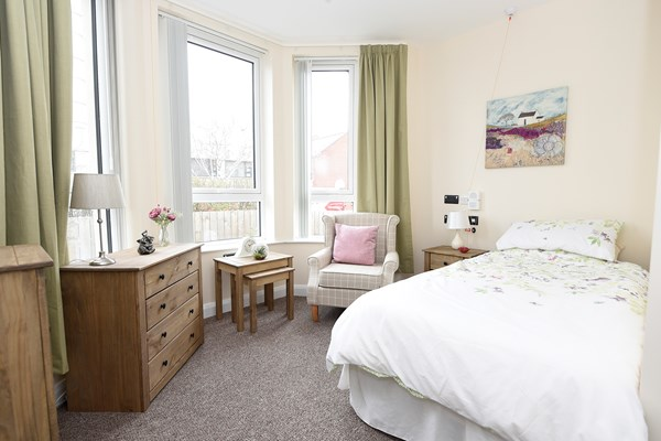 A large bright bedroom with oak furniture and sage green curtains