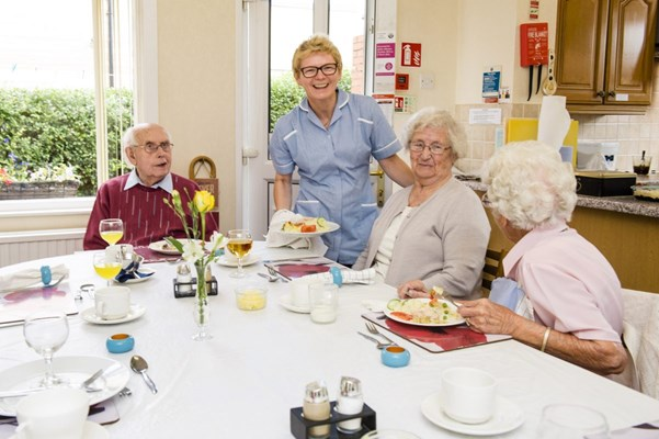 A member of staff is stood with residents who are sat around the table having lunch
