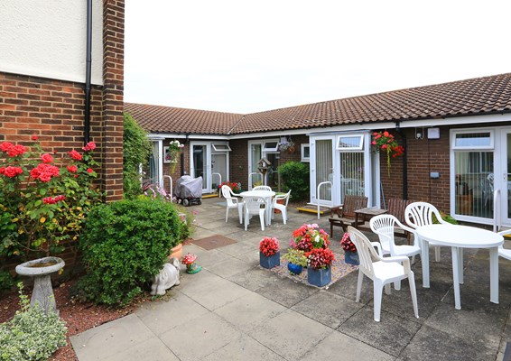 Beautiful garden with paved floors and plenty of seating where residents can enjoy the sunshine