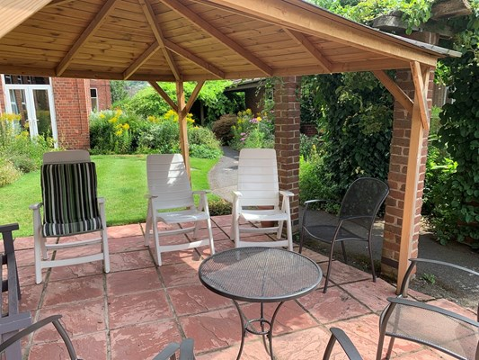 A wooden gazebo with seating area