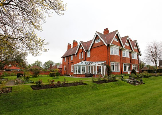 Large red bricked house with a conservatory and large garden