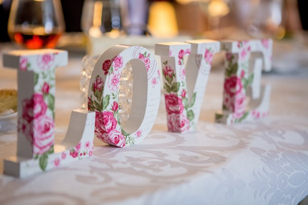 A love sign made from wooden letters with pink flowers