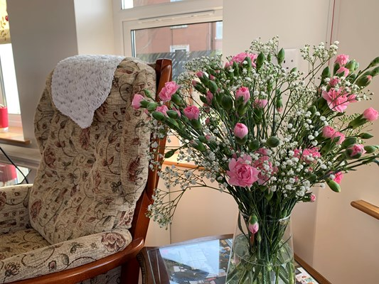 A vase of pink flowers on a table beside a chair
