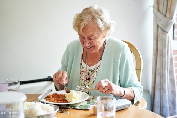 Resident tucking into a delicious home cooked meal
