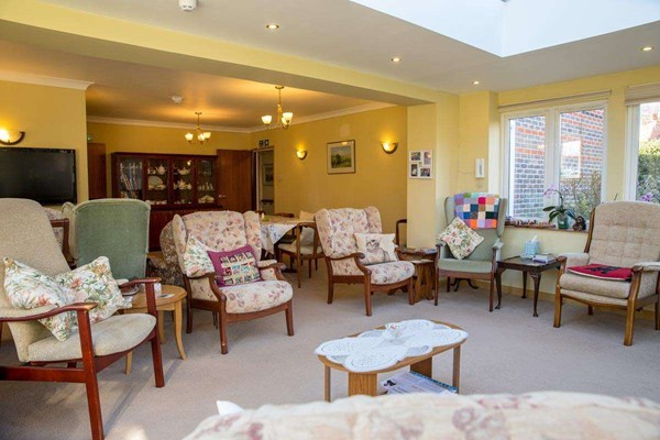 Spacious lounge area with ample seating for residents to relax at Abbeyfield House Alfriston
