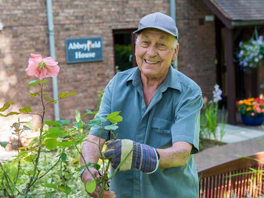 Happy resident in the garden at Abbeyfield House, Great Missenden, pruning a pink rose