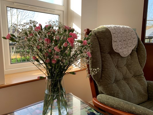 A vase of pink flowers on a table beside an armchair