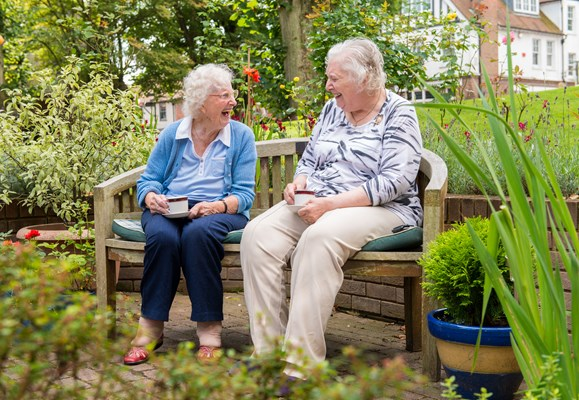Two residents having fun catching up sitting on a bench in the garden whilst enjoying a cup of tea