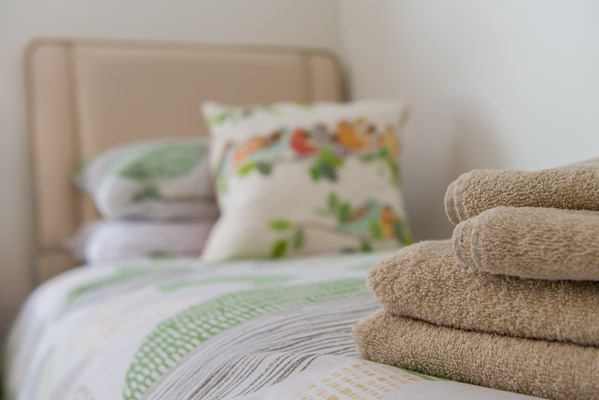 Freshly folded towels on the end of bed at Abbeyfield House, Great Missenden