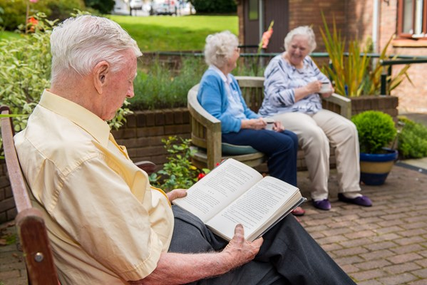 Resident enjoying a book on a bench in the garden with two other residents catching up on another bench