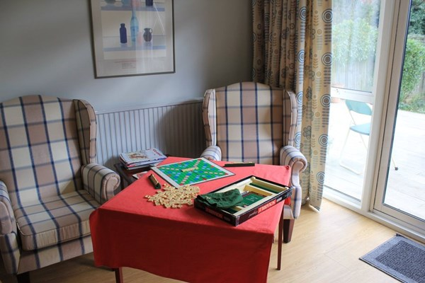 Armchairs by the window with a game of scrabble set up for residents to play together