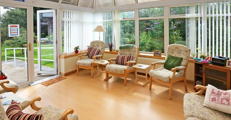 A bright conservatory with seating for the residents