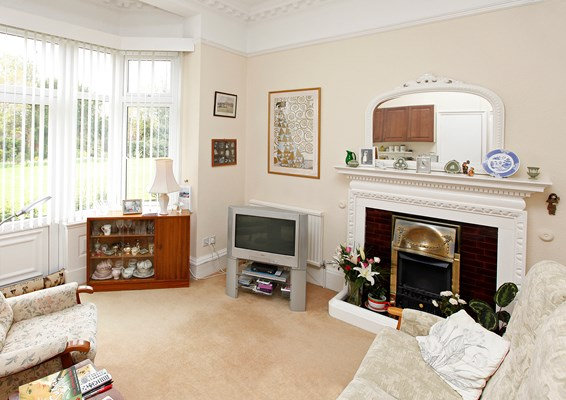 The house TV room brightly decorated with a large fireplace