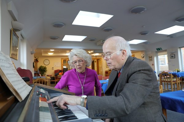 Resident sitting at the keyboard playing music together