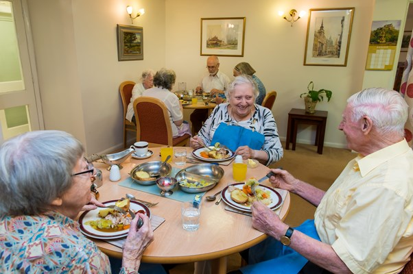 Residents sitting round the tables in the communal dining room enjoying a meal together
