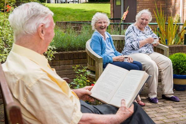 Residents in the garden sitting on benches enjoying a catch up