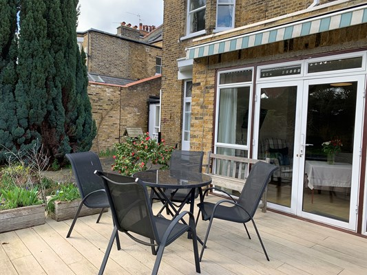 Table and chairs outside on the decking where residents can enjoy the sunshine in the garden