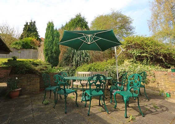 Table and chairs outside in the garden where residents can enjoy the sunshine at Warburton and Clarisse Lodge