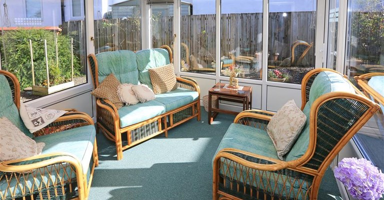 Bright sunny conservatory with green carpet and sofas