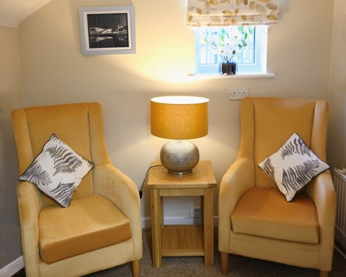 Snug area with two yellow chairs and a lit table lamp