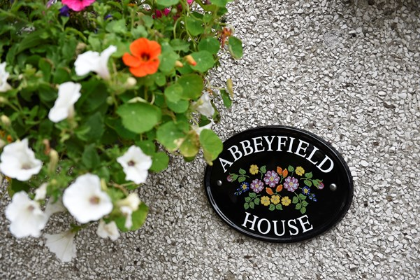 An Abbeyfield House sign on the wall behind a colourful hanging basket of flowers