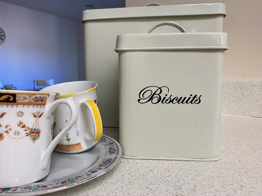 Close up of some mugs and a biscuit tin
