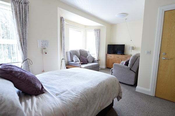 A bright bedroom with a bed, sofas and a television