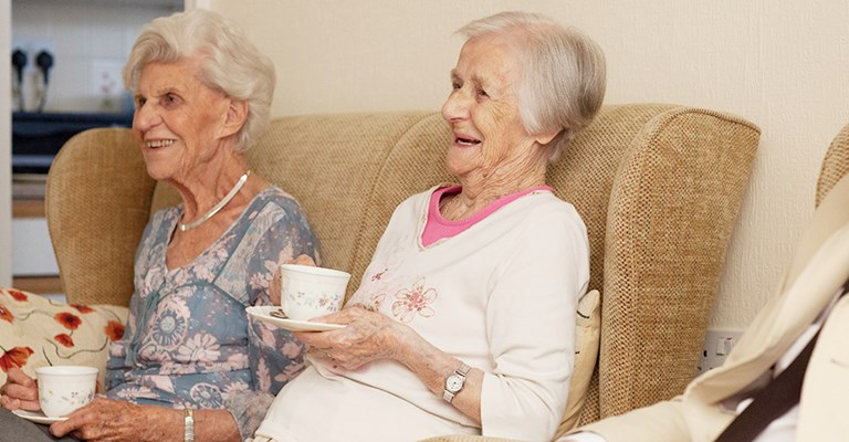 Smiling, happy residents sitting together enjoying a cup of tea