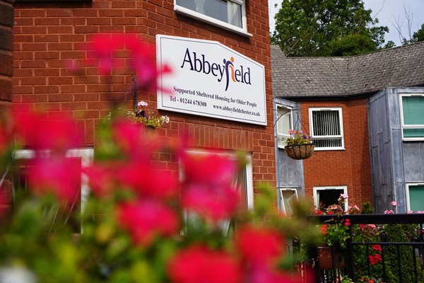 A view of the Abbeyfield sign on the house through some pink flowers