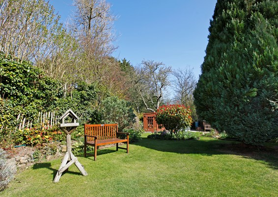Bright and sunny garden with bench and summer house at Abbeyfield House
