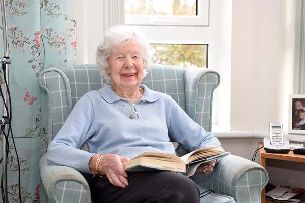 A resident is smiling for a photo with a book on her lap