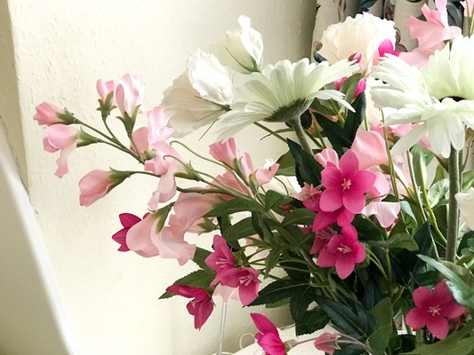 Beautifully arranged white and pink flowers in a vase on the windowsill at Abbeyfield House, Sutton