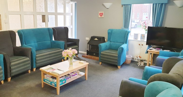 Beautiful blue and grey lounge where residents can relax, catch up with friends and family or socialise with other residents