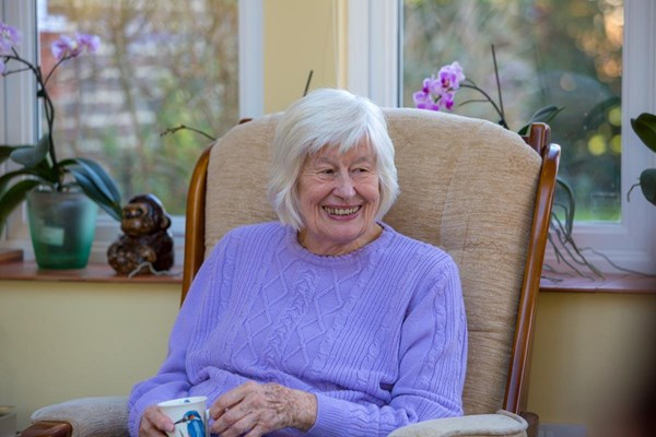 Smiling resident sitting in chair holding a cup of a tea at Abbeyfield House