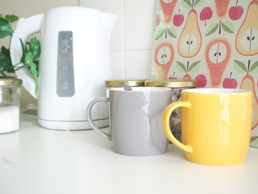 Yellow and grey mugs sat beside a kettle