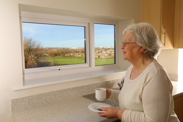 A lady enjoys the beautiful view from her kitchen