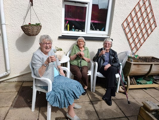Three ladies sit outside in the sun with refreshments