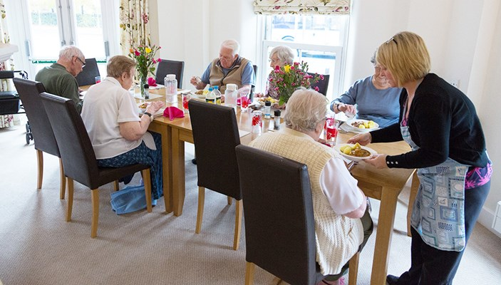 Residents in the communal dining room sharing a delicious home cooked meal together