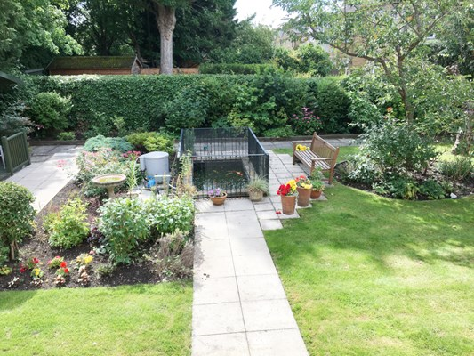 Sunny garden with paved pathways, pond, bird bath and bench where residents can enjoy nature