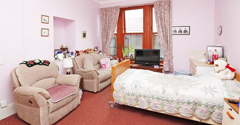 Pink bedroom with bed and two armchairs