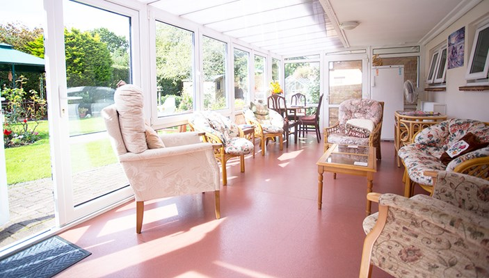 Bright and sunny conservatory where residents can socialise, relax and enjoy views of the lovely garden