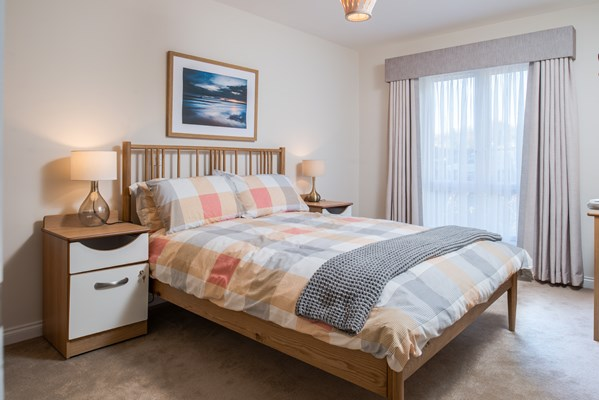 A large double bed with bed side tables and lamps