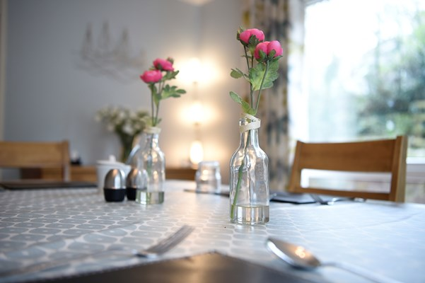 A close up of a dining table set for dinner with pink flowers in glass bottles