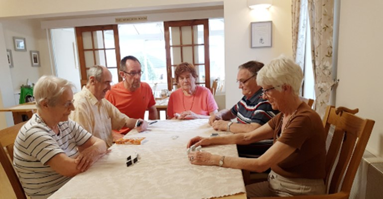 Residents sit around a table playing games
