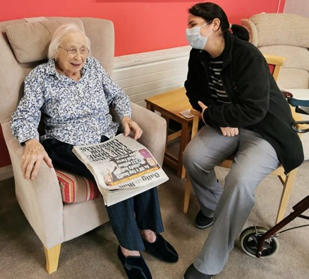 A member of staff is sat talking to a resident